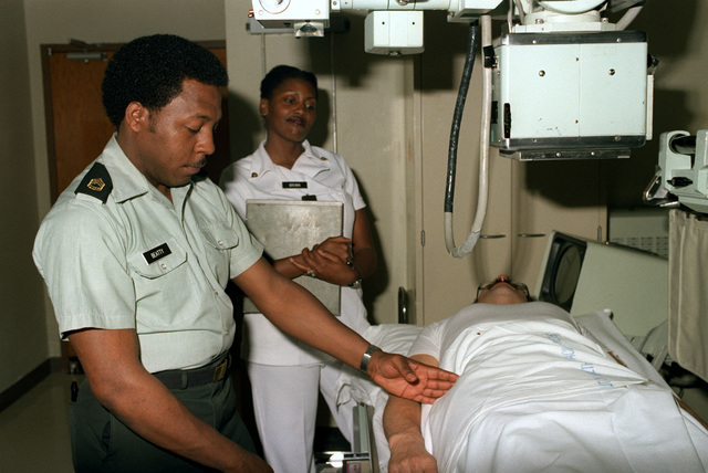 Sergeant First Class William A. Beatty, a radiology specialist, shows SPECIALIST 4 Debra Brown the proper way to position a patient for an X-ray, at the Eisenhower Army Medical Center. They are members of the 3297th Medical Company