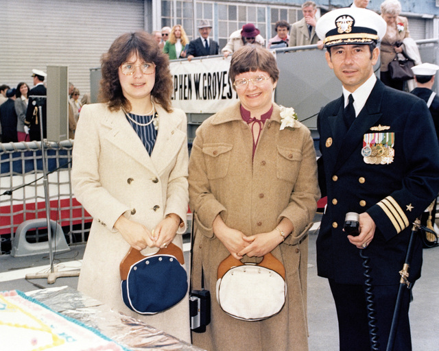 Susan Groves Mills, matron of honor, left; Mrs. Miriam Groves Landry, sponsor's proxy; and Commander (CDR) Philip Bozzelli, prospective commanding officer, stand aboard the Oliver Hazard Perry class guided missile frigate USS STEPHEN W. GROVES (FFG 29) at the conclusion of the commissioning ceremony