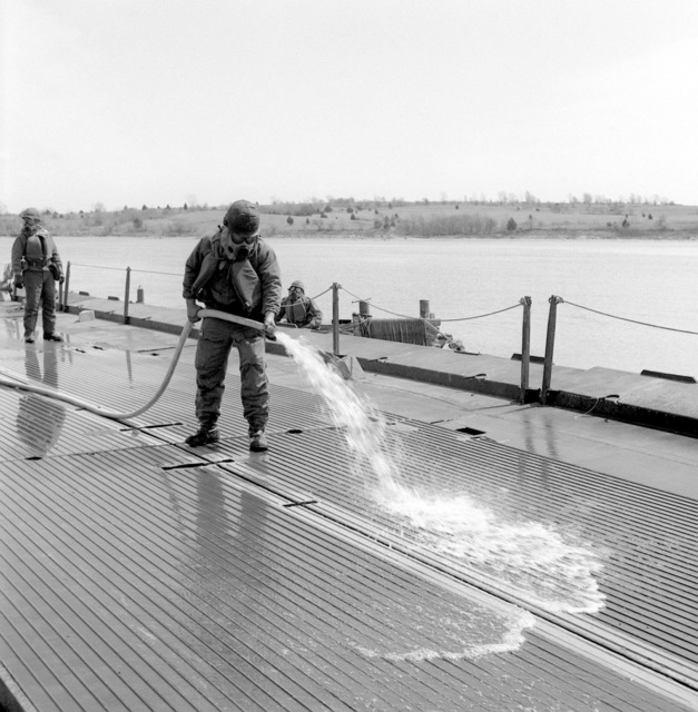 A member of the 34th Engineer Battalion wears potective gear while washing down the deck of a Class-70 ribbon bridge during a training exercise conducted under simulated NBC (Nuclear, Biological Chemical) conditions