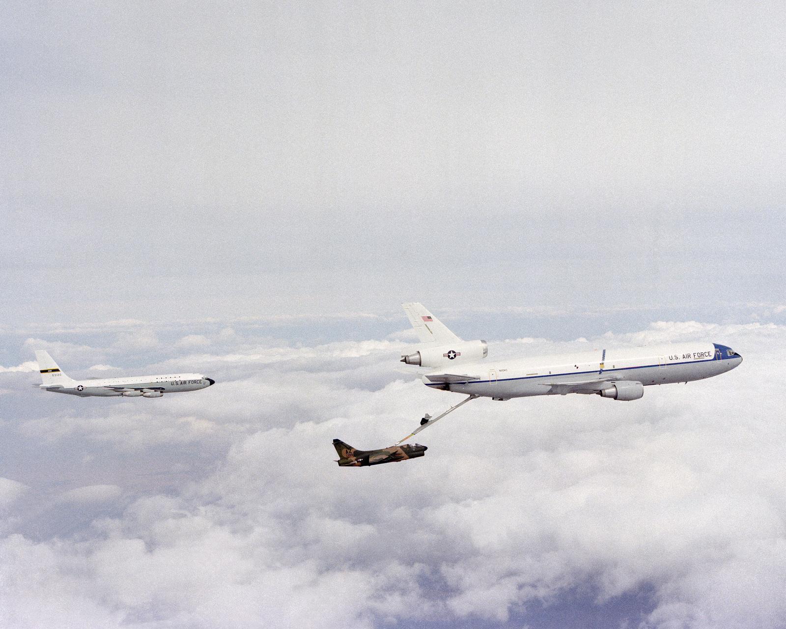 A view of a KC-10A Extender aircraft refueling an A-7D Corsair II aircraft in flight. A KC-135 Stratotanker aircraft is visible behind them