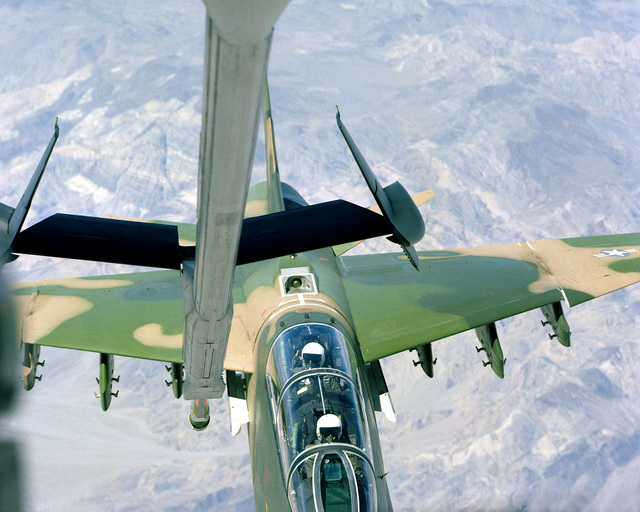 A view of an A-7K Corsair II aircraft as it maneuvers into position to be refueled by a KC-10A Extender aircraft in flight