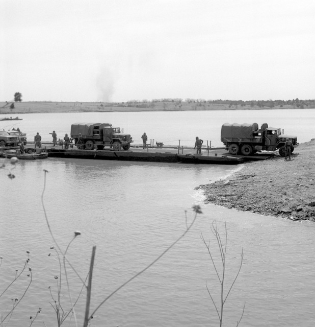 Members of the 34th Engineer Battalion ferry trucks across Lake Milford aboard a Class-70 ribbon bridge raft during a training exercise conducted under simulated NBC (Nuclear, Biological, Chemical) conditions