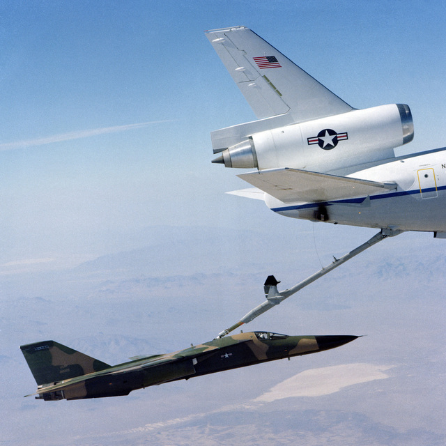 Right side view of a KC-10A Extender aircraft (tail section) refueling an F-111 Fighter aircraft in flight