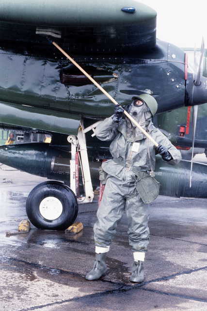 """A ground crewman """"decontaminates"""" an OV-10 Bronco aircraft after it """"had flown through a chemical environment"""" during Exercise UREX '82"""