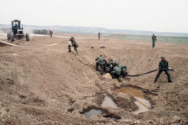 "A rapid runway repair team from the 601st Civil Engineering Squadron prepares to drain a ""bomb crater"" by using a pump, during Exercise UREX '82"