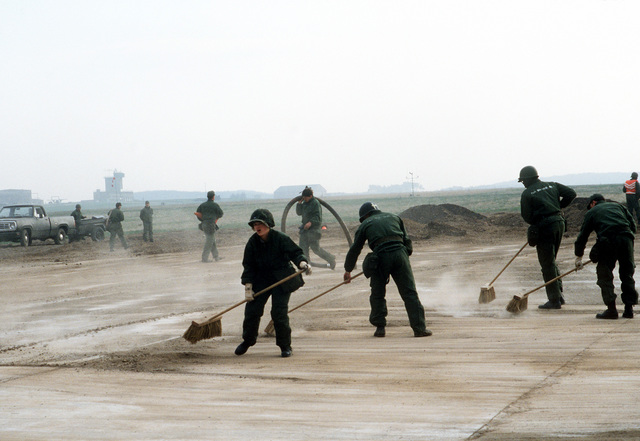 "A rapid runway repair team from the 601st Civil Engineering Squadron sweeps dirt off of a runway after a ""bomb crater"" is filled in, during Exercise UREX '82"