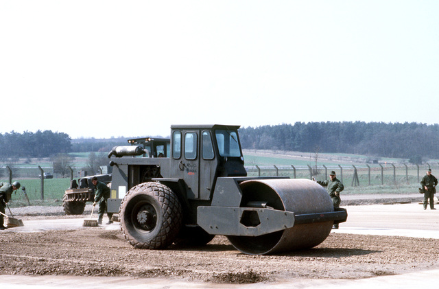 "A rapid runway repair team member from the 601st Civil Engineering Squadron operates heavy equipment to level the dirt used to fill in a ""bomb crater"", during Exercise UREX '82"