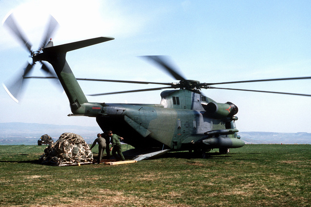 A right rear view of a CH-53C Super Jolly helicopter from the 601st Tactical Air Support Squadron, as preparations are made to onload a pallet through its cargo opening during Exercise UREX '82