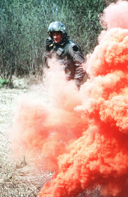 MAJ Ed Kroboth of the 704th Tactical Airlift Squadron uses a smoke bomb to signal a search and rescue helicopter to his position as he acts as a downed pilot during Exercise UREX '82