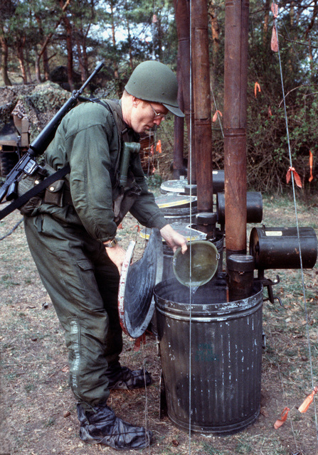 MSGT Jim Paler, non-commissioned officer in charge of site support for the 622nd Tactical Control Flight, dips a helmet into a barrel of hot water to clean his mess kit, during Exercise UREX '82