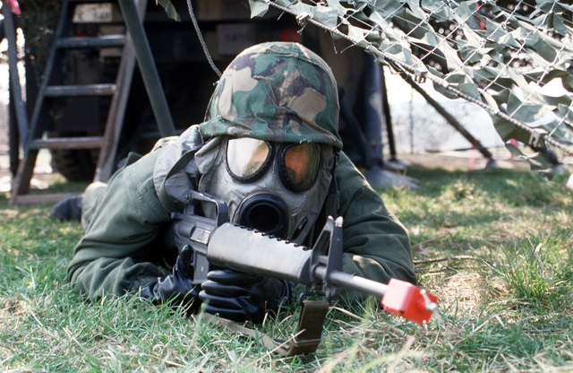 """SGT Debra Rivera, wearing chemical warfare gear and armed with an M-16A1 rifle, secures her assigned position during condition """"Black"""" of the simulated chemical warfare attack, taking place as part of Exercise UREX '82"""