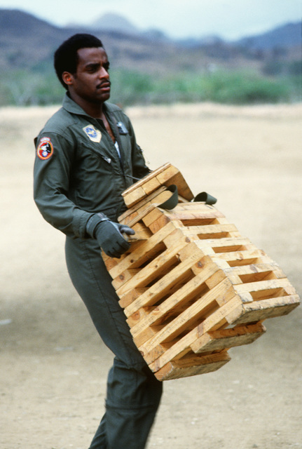 A loadmaster moves blocks into position for loading cargo aboard a C-130 Hercules aircraft during exercise Ocean Venture '82