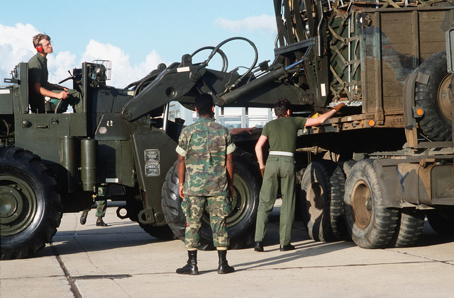 Members of the 5th Aerial Port Squadron unload cargo from a C-141 Starlifter aircraft and use a forklift to load the cargo aboard a trailer truck during exercise Ocean Venture '82