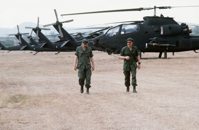 SSGT Rodney Chaplin and CPT Wallace Jenkins, left to right, walk on the flight line during exercise Ocean Venture '82. The men are members of the 17th Air Cavalry Regiment, 101st Airborne Division