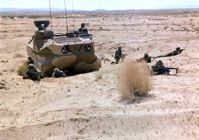 Six combat-ready Marines from Company B, 1ST Battalion, 4th Marines, set up a hasty defensive perimeter around their tracked personnel landing vehicle (LVTP-7)