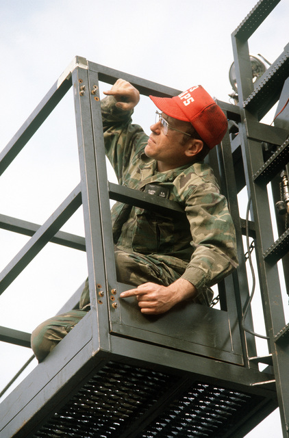 A ground crewman points to the new cage door hinges on a Cochran elevator loader used for loading equipment aboard a 747 cargo aircraft during Operation Ocean Venture '82