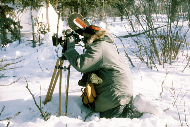 A motion picture specialist shoots 16mm film footage during Exercise Cool Snowhog '82