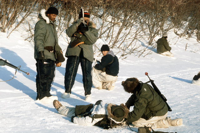 "A motion picture specialist shoots 16mm film footage of a ""wounded"" soldier during Exercise Cool Snowhog '82"