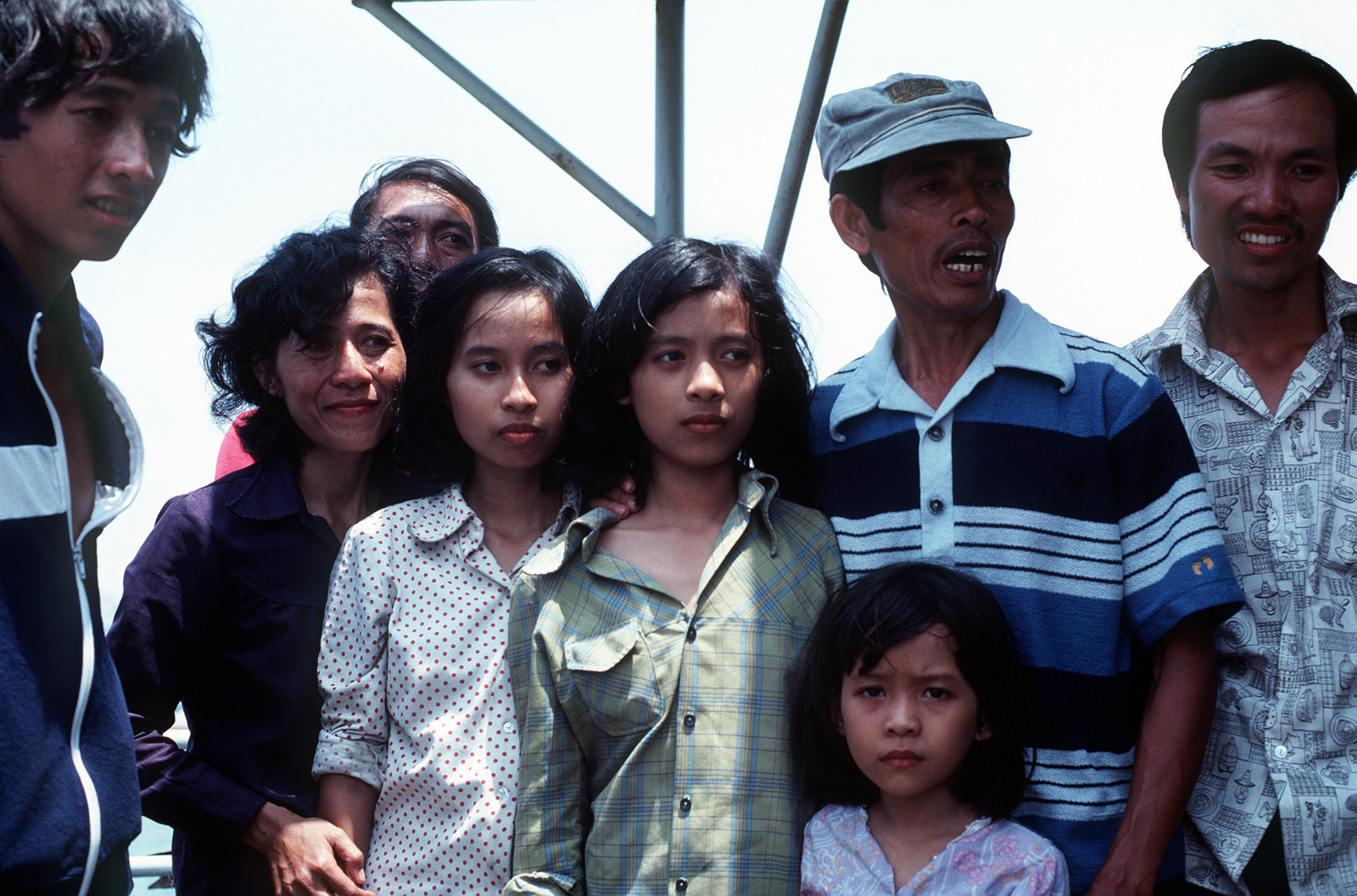 A Vietnamese man and members of his family wait to disembark from the Military Sealift Command merchant ship USNS MASON LYKES. They were among a group of 59 refugees who were rescued from a small boat in the open ocean by the crew of the MASON LYKES