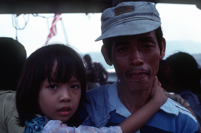 A Vietnamese refugee and his daughter wait to disembark from the Military Sealift Command merchant ship USNS MASON LYKES. They were rescued by the MASON LYKES, along with 57 other refugees, from a small boat in the open ocean