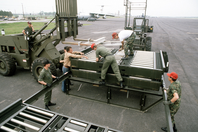 Ground crewmen assemble a Cochran elevator loader to be used for loading equipment aboard a 747 cargo aircraft during Operation Ocean Venture '82