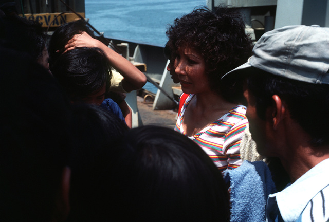 Interpreter Le Kyle talks with several Vietnamese refugees aboard the Military Sealift Command merchant ship USNS MASON LYKES. The refugees are part of a group of 59 who were rescued from a small boat in the open ocean by the crew of the MASON LYKES