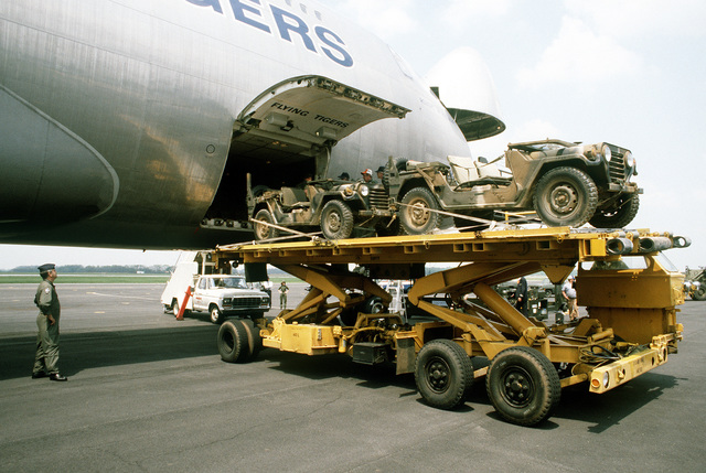 Jeeps are transferred from a K-loader through the lower front compartment door of a 747 cargo aircraft during Operation Ocean Venture '82