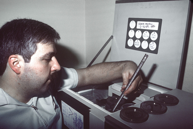 PH1 Tom Berault, USNR, checks the chemistry in the Image Maker EH11OA universal processor for proper temperature before processing black and white film at the Pacific Fleet Audiovisual Facility