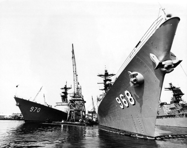Two Spruance class destroyers in dry dock. To the right, a starboard bow view of the destroyer USS ARTHUR W. RADFORD (DD-968), overhaul completed, and to the left, a port bow view of the destroyer USS CARON (DD-970), recently arrived to begin overhaul procedures