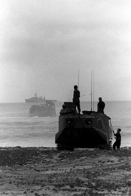 An LVTP-7 tracked landing vehicle comes ashore during a beach assault, part of Operation Ocean Venture '82. The dock landing ship USS THOMASTON (LSD-28) is in the background