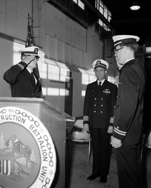 LT. j. g. Bill Galloway, left, is relieved as commanding officer of Construction Battalion Unit 417 by LT. MAC Thigpen, at right