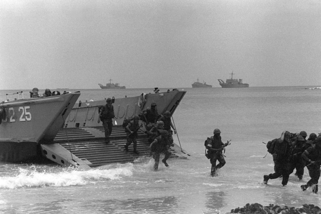Marines from the Fourth Marine Amphibious Brigade disembark from an LCM-8 mechanized landing craft during a beach assault taking place during Operation Ocean Venture '82. Tank landing ships and a dock landing ship are visible in the background