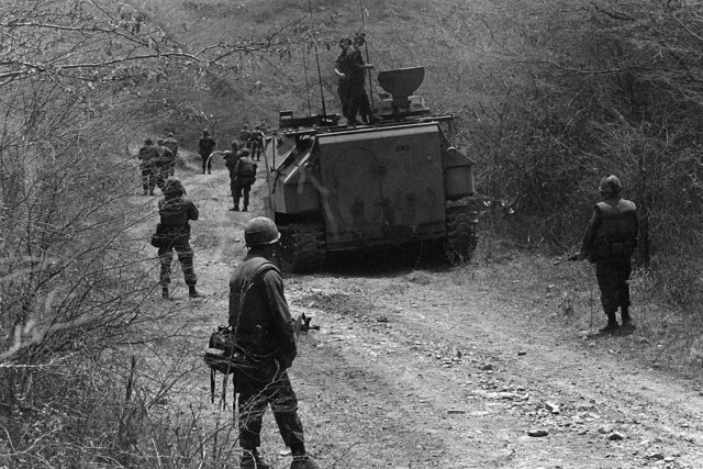 Marines from the Fourth Marine Amphibious Brigade move inland, around an LVTP-7 tracked landing vehicle, during an assault on the beach taking place during Operation Ocean Venture '82