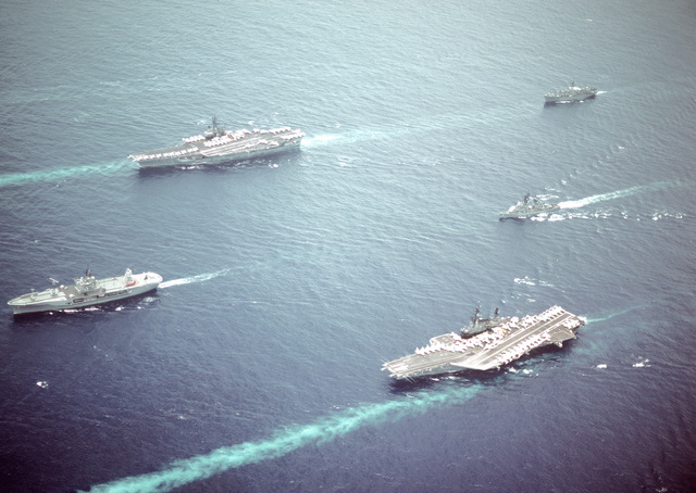 Aerial port view of part of Task Group 70 underway. The ships in the Task Group are: (clockwise from the lead ship) the amphibious command ship USS BLUE RIDGE (LCC-19), the aircraft carrier USS RANGER (CV-61), the combat store ship USS SAN JOSE (AFS-7), the guided missile destroyer USS JOSEPH STRAUSS (DDG-16) and the aircraft carrier USS MIDWAY (CV-41)
