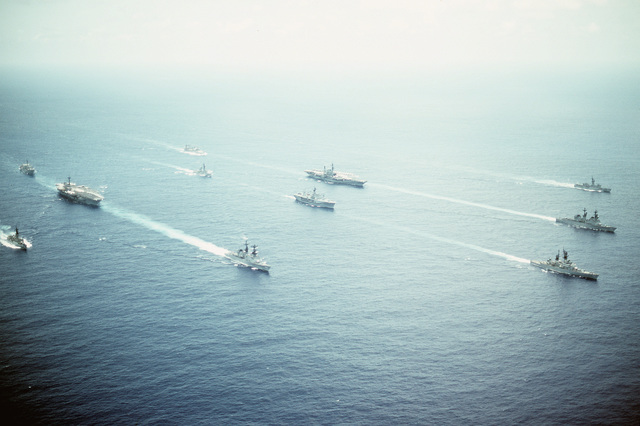 Aerial starboard bow view of part of Task Group 70, including the amphibious command ship USS BLUE RIDGE (LCC-19) and the aircraft carrier battle groups USS RANGER (CV-61) and MIDWAY (CV-41) underway