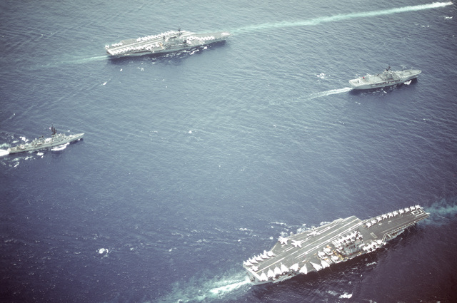 Aerial starboard view of part of Task Group 70 underway. The ships are: (clockwise from the lead ship) the amphibious command ship USS BLUE RIDGE (LCC-19), the aircraft carrier USS RANGER (CV-61), the guided missile destroyer USS JOSEPH STRAUSS (DDG-16) and the aircraft carrier USS MIDWAY (CV-41)