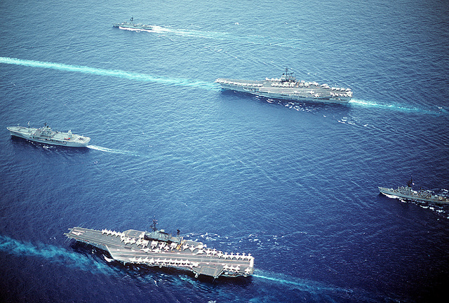 An aerial port view of part of Task Group 70 underway. Some of the ships included are the aircraft carrier USS MIDWAY (CV-41), foreground, the amphibious command ship USS BLUE RIDGE (LCC-19), left, and the aircraft carrier USS RANGER (CV-61), background