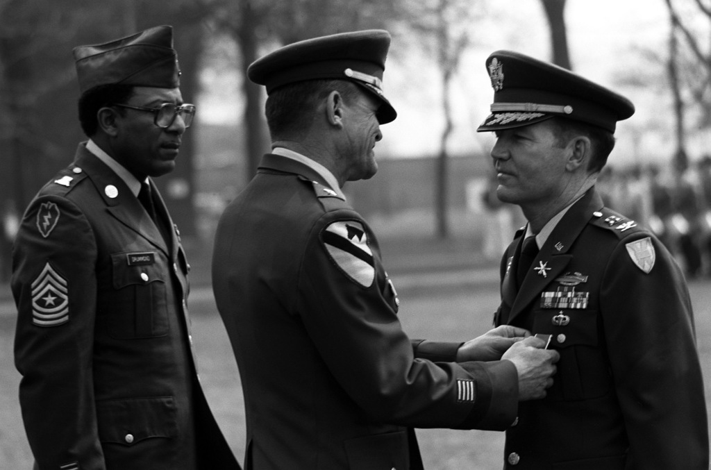 Brigade General George R. Stotser presents the Legion of Merit medal to Colonel Gerald McConnell. Observing the ceremony is STAFF Sergeant Major Cepha Drummond