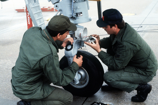 Two reservists from 104th Tactical Fighter Wing, Massachusetts Air National Guard, repair a headlight on an A-10 Thunderbolt II aircraft during a reserve rescue exercise