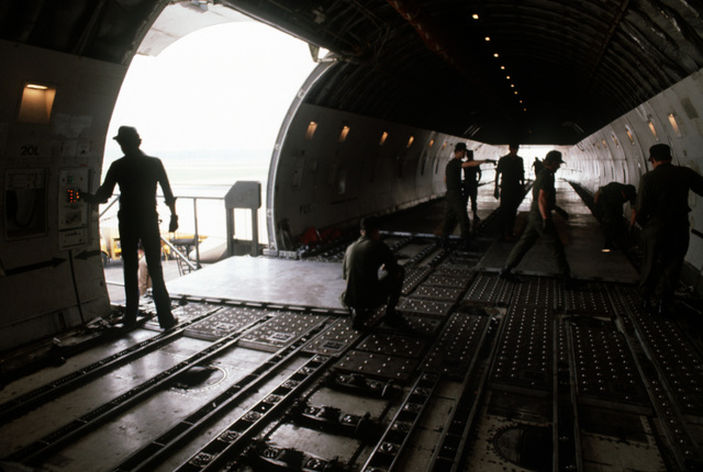 A floor of metal pallets is laid by ground crewmen in preparation for the loading of equipment through the side rear door of a 747 cargo aircraft during Operation Ocean Venture '82
