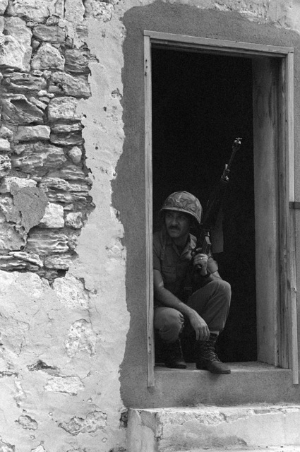 A Puerto Rican National Guardsmen, carrying an M-16A1 rifle, takes shelter in a doorway during Operation Ocean Venture '82