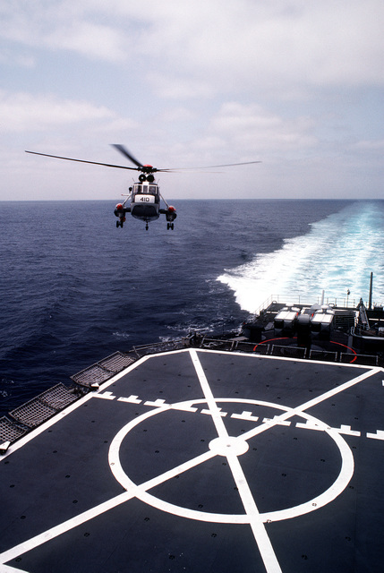 A SH-3 Sea King helicopter approaches the flight deck of the Spruance class destroyer USS INGERSOLL (DD-990), during at-sea landing qualifications for Reserve Helicopter Anti-submarine Squadron 84 (HS-84)
