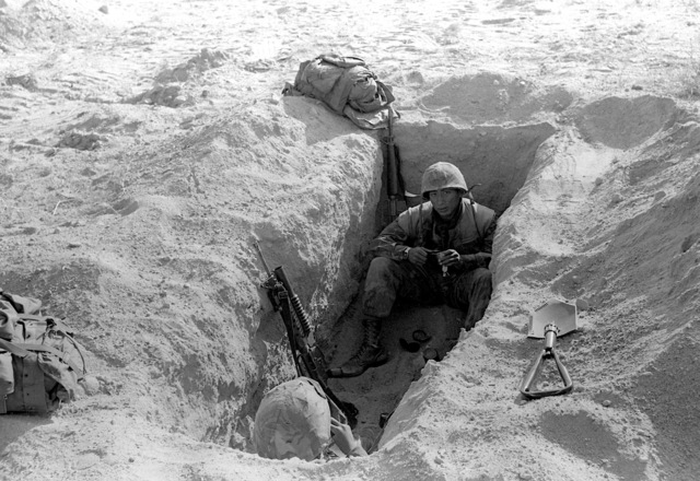 During Operation CAX 6-82, LCPL Mendez and his buddy from 2nd Battalion, 1ST Marines, 1ST Marine Division, Fleet Marine Force, takes times to eat C-rations after digging their two-man fighting hole