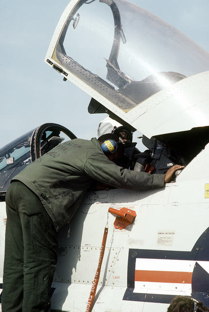 A crewman from Light Attack Squadron 122 (VA-122) performs a preflight check on an A-7 Corsair II aircraft