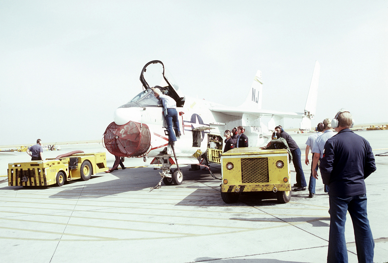 Crewmen from Light Attack Squadron 122 (VA-122) perform preflight maintenance on an A-7 Corsair II aircraft