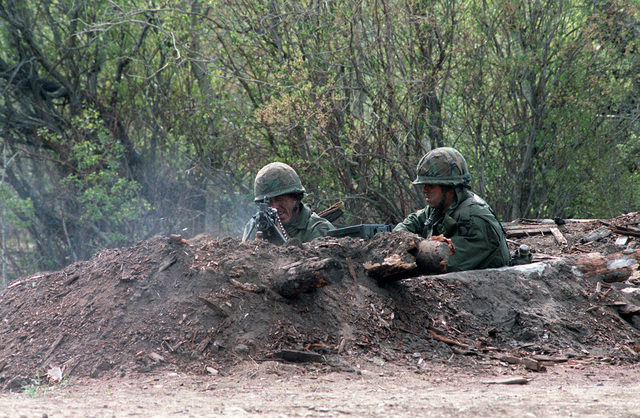 An M-60 machine gun crew from the 3rd Bn., 327th Inf., 101st Abn. Div., fires blank rounds from a foxhole while participating in a mock battle during the combined U.S./Canadian NATO Exercise Rendezvous '83