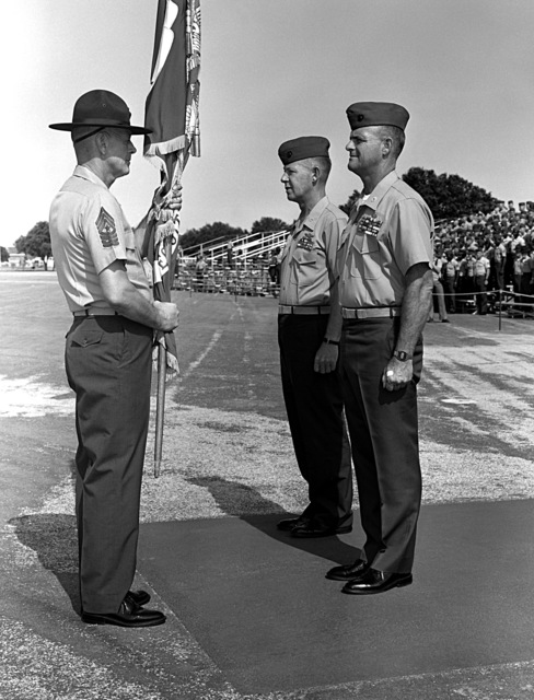 COL Bowin prepares to take the regimental colors from MSGT Walls, so they can be given to COL Donald J. Myers, center, who is relieving Bowin as the commanding officer