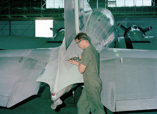 SGT M.A. Grindley helps to prepare this Douglas C-117 aircraft, No. 833, for its retirement flight by drilling a hole in the section to replace a cover