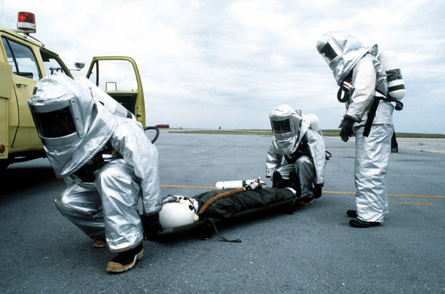 "An ""injured"" space shuttle commander is carried on a stretcher by a recovery team wearing protective clothing during a contingency and planning exercise"