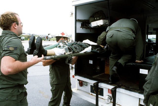 "An ""injured"" space shuttle commander is transferred to an ambulance that will take him to the Naval Regional Medical Center at Camp Lester, during a contingency and planning exercise"